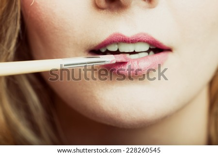 Cosmetic beauty procedures and makeover concept. Closeup part of woman face pink lips. Make-up artist applying lipstick with accessories tools. - stock photo