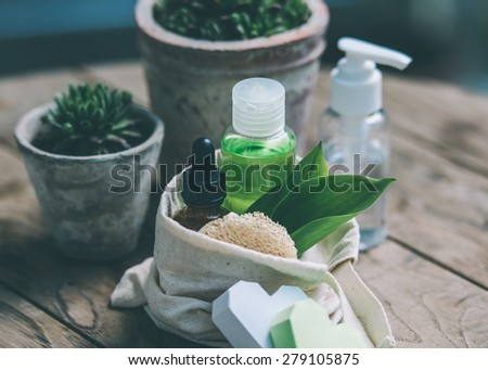 Cosmetic bottle containers with green herbal leaves and garden pots with flowers on wooden background. Toned image - stock photo