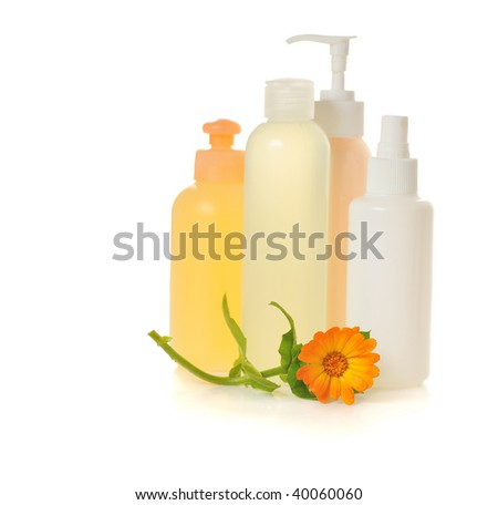 cosmetic bottles with flower of calendula isolated on white