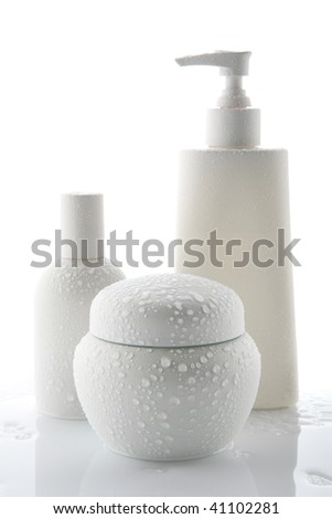 Cosmetic bottles with water drops on a white background - stock photo