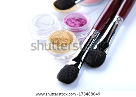 Cosmetic brushes and crumbly eyeshadows, close-up