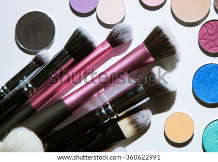 Cosmetic brushes and shadows, closeup shot - stock photo