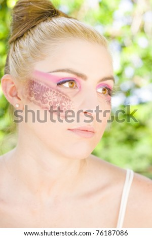 Cosmetic Concept Of The Face Of An Attractive Young Blonde Woman In Colourful And Bright Lace Makeup Daydreaming Outdoors - stock photo
