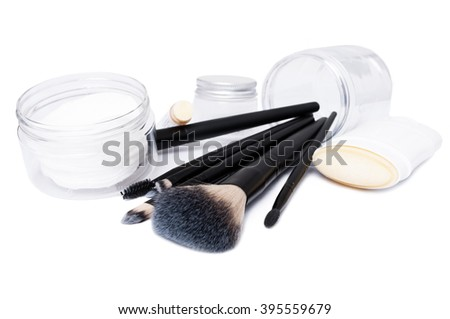 Cosmetic concept with face brushes, stick deodorant, lip moisturizer and transparent plastic jars or containers - stock photo