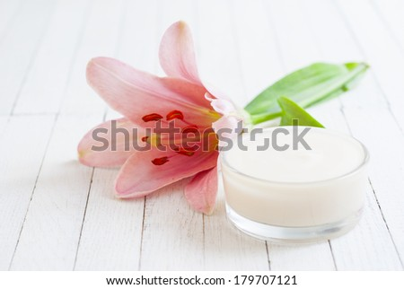 cosmetic cream and pink lily flower on white wooden