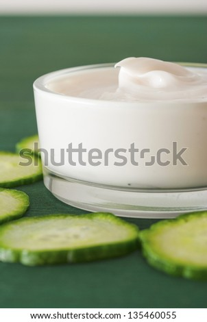 cosmetic cream in glass jar with cucumber slices, wood table