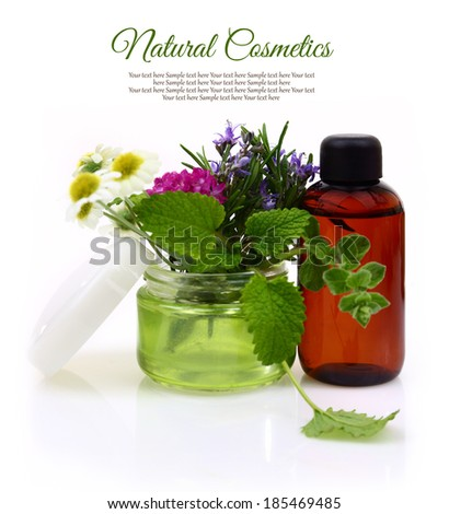 Cosmetic cream jar with herbs inside and essential oil bottle  - stock photo