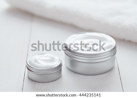 Cosmetic cream lotion white organic beauty moisturizer cleansing acne product with towel on white background. Dermatology hygienic anti aging, wrinkles, blemish, pimples, blackheads clear treatment - stock photo