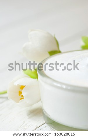 cosmetic cream with jasmine blossom on white wooden table