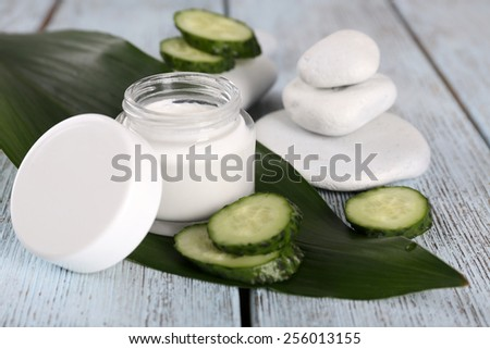 Cosmetic cream with slices of cucumber and spa stones on wooden background - stock photo
