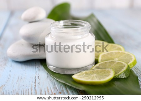Cosmetic cream with slices of lime and spa stones on wooden background - stock photo
