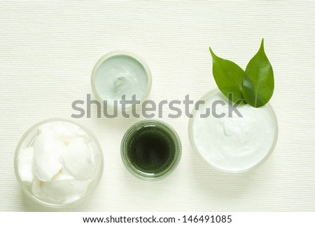 cosmetic creams on white textile, top view