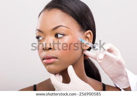 cosmetic doctor injecting african woman face close up - stock photo