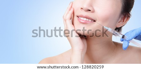 Cosmetic injection in the female face. Lips zone. Isolated on blue background, asian beauty woman - stock photo