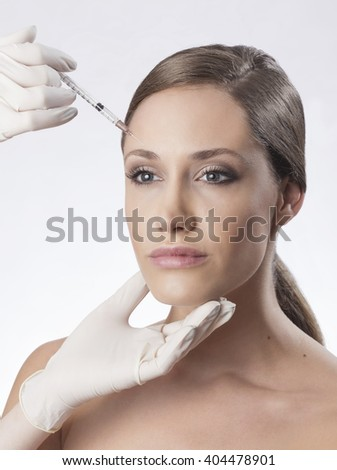 Cosmetic injection of botox to the pretty female face. Isolated on white background - stock photo