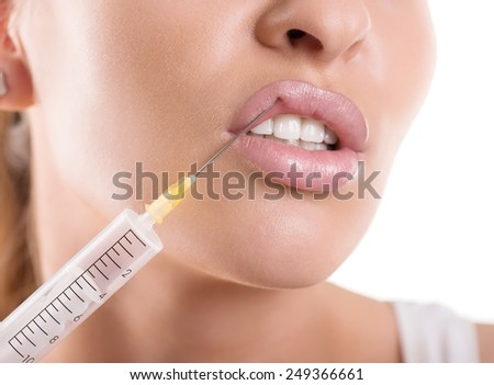 cosmetic injection to the lips of a beautiful woman, isolated on white