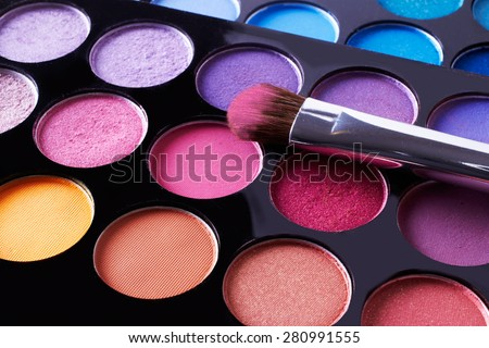 Cosmetic.Makeup with pink eye shadow powder on the brush. Close up macro.Eye-shadow pallet for professional make up artist.
