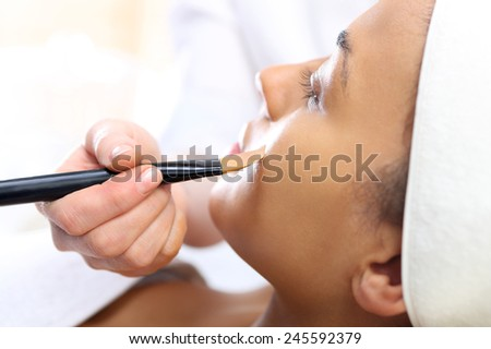Cosmetic moisturizing mask is applied to the face of a woman. Cosmetic procedure woman's face in the mask mitigating and cucumber slices on eyes  - stock photo