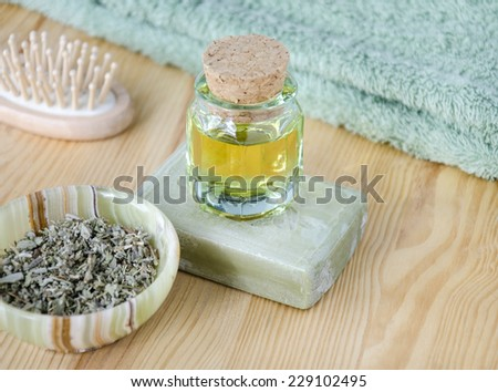 Cosmetic oil, organic soap and dried herbs for skincare and hair - stock photo
