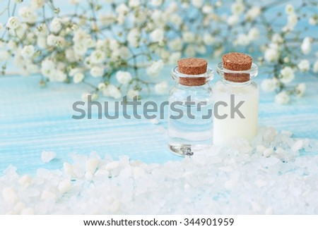Cosmetic spa bottles with tonic and lotion, sea salt, turquoise background. Soft light focus - stock photo