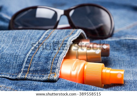 Cosmetic sunscreen products in jeans pocket on the background of sunglasses. Skin care cosmetics containing sun protection factor - stock photo
