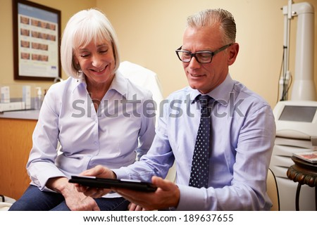 Cosmetic Surgeon Discussing Proceedure With Client In Office - stock photo