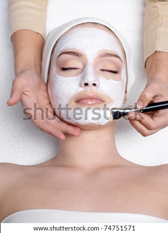 Cosmetician applying facial mask to the face of young beautiful woman in spa salon - vertical - stock photo