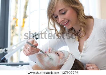 Cosmetician applying facial skincare mask to customer - stock photo