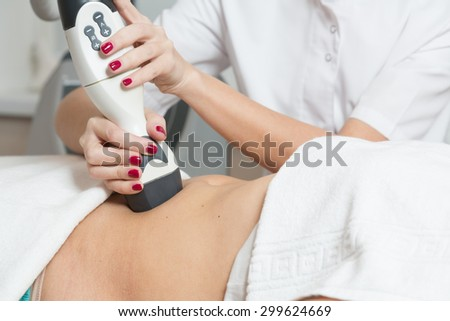 Cosmetician  making procedure of lymphatic drainage with a professional equipment - stock photo