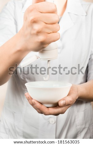 Cosmetician squeezes cream out of a tube into cup. - stock photo