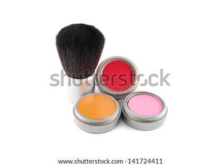 Cosmetics: A blush brush and three different colors of blush.