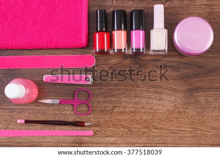 Cosmetics and accessories for manicure or pedicure, nail file, nail polish and remover, scissors, nail clippers, fluffy towel, concept of nail care, copy space for text - stock photo