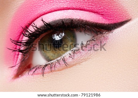 Cosmetics and beauty care. Macro close-up of beautiful green female eye with bright fashion runway make-up. Pink eyeshadows and black eyeliner