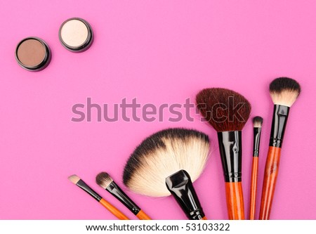 Cosmetics and brushes for a make-up on a pink background - stock photo