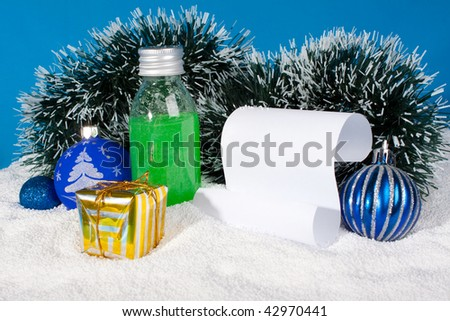 Cosmetics and Christmas knickknacks on snow with a paper template for congratulations.