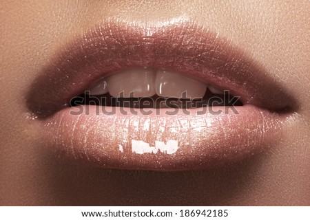 Cosmetics and makeup. Closeup shoot of beautiful lips of woman with beige lipstick and gloss. Sexy wet lip make-up. Sweet kiss. Close-up of beautiful full lips