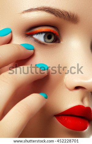 Cosmetics and makeup. Woman's face with vivid makeup and colorful nail polish. Trendy maleup. Close-up portrait of fashion model girl with red lips and mint manicure. Smoky eyes and long eyelashes.