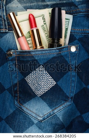 Cosmetics and money sticks out of the pocket of his jeans with rhinestones, as background