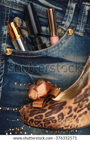 Cosmetics and perfumery sticks out of the pocket of his jeans, as background - stock photo