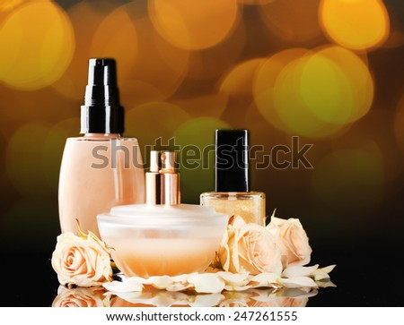 Cosmetics and roses on bright festive background - stock photo