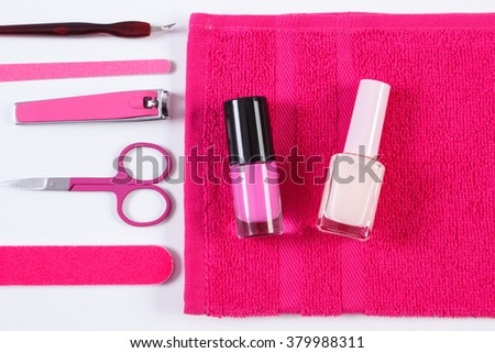 Cosmetics and set of manicure or pedicure tools, nail file, nail polish, scissors, nail clippers, fluffy towel, concept of nail care - stock photo