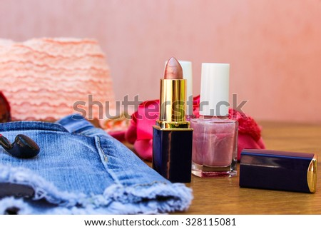 Cosmetics and women's accessories: lip gloss, nail polish, hat, denim shorts and headphones on table - stock photo
