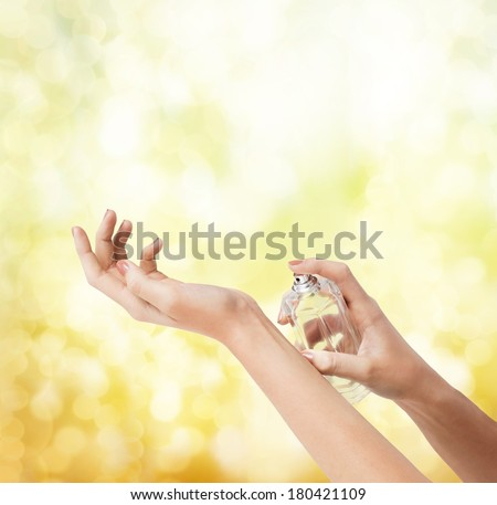 cosmetics, body parts and beauty concept - close up of woman hands spraying perfume - stock photo