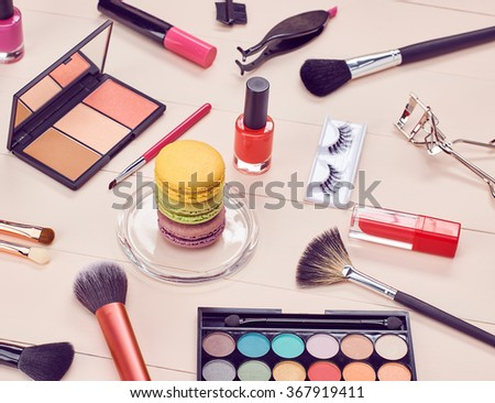 Cosmetics.Fashion cosmetics woman essentials. Beauty makeup accessories.Macarons french dessert,cosmetic . Lipstick, brushes, eyeshadow, eyelashes, mascara.Unusual creative cosmetic set. Vanilla wood.