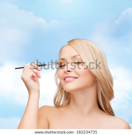 cosmetics, health and beauty concept - beautiful woman with closed eyes and makeup brush - stock photo