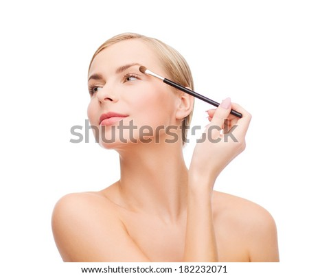 cosmetics, health and beauty concept - beautiful woman with makeup brush - stock photo