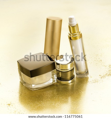 Cosmetics in gold environment with small gold nuggets - stock photo