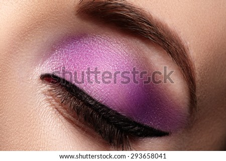Cosmetics & make-up. Beautiful female eye with sexy black liner and bright purple makeup. Fashion classic arrow shape on woman's eyelid. Chic evening make-up  - stock photo