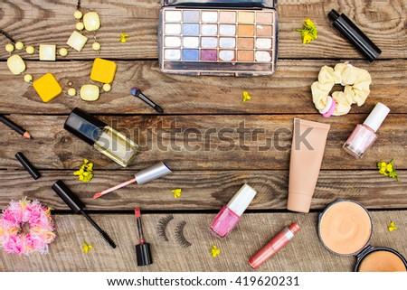 Cosmetics: mascara, beads, elastic hair band, false eyelashes, concealer, nail polish, perfume, eyeliner, powder, lip gloss, eye shadow and  yellow flowers on wooden background. Toned image.  - stock photo