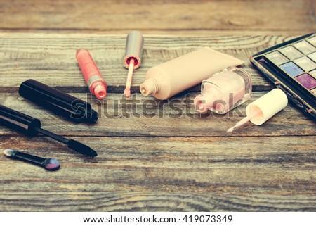 Cosmetics: mascara, concealer, nail polish, perfume, lip gloss and eye shadow on wooden background. Toned image.  - stock photo